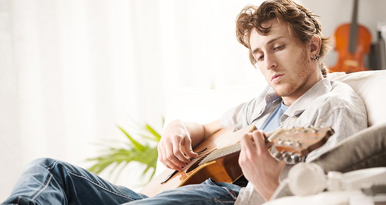Songwriter Composing A Song On Acoustic Guitar