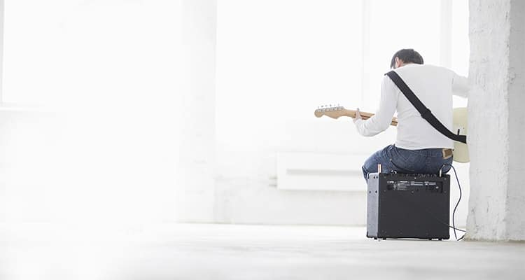A man sitting on a guitar amp practising playing an electric guitar